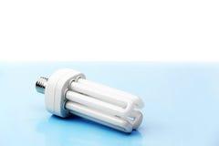 Ampoule économiseuse d'énergie sur le fond bleu Images stock