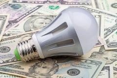 Ampoule électrique de LED sur le dollar photographie stock