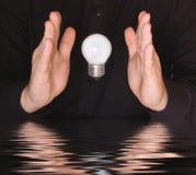 Ampoule électrique volante entre les paumes Photo libre de droits
