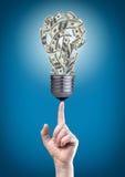 Ampoule avec de l'argent sur l'extrémité du doigt photo stock