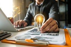 Ampoule avec la main d'affaires fonctionnant avec l'ordinateur portable a photographie stock libre de droits