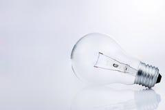 Ampoule avec la réflexion sur le blanc. Photographie stock libre de droits