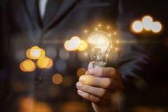Ampoule avec le cerveau les mains de l'homme d'affaires image stock