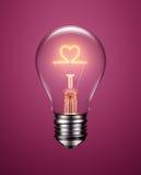 Ampoule avec le filament formant une icône de coeur Photographie stock libre de droits