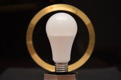 Ampoule blanche sur le fond noir avec le cercle d'or Photo libre de droits