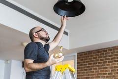 Ampoule changeante d'homme à la maison images libres de droits