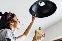 Ampoule changeante de femme à la maison Image libre de droits
