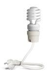 Ampoule économiseuse d'énergie avec la prise d'isolement sur le blanc, chemin Images libres de droits