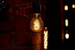 Ampoule d'Edison accrochant sur un long fil Lumière jaune chaude confortable rétro Photographie stock