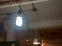 Ampoule de bobine fluorescente lumineuse accrochant dans l'entrepôt image stock