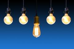 Ampoule de cru accrochant au-dessus du fond bleu-foncé, concept d'idée photographie stock