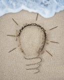 Ampoule dessinée sur la plage de sable avec la mousse blanche de vague Images stock