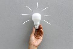 Ampoule et main Photographie stock libre de droits