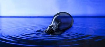 Ampoule flottant sur l'eau avec l'effet de la lumière discret en studio Photo libre de droits