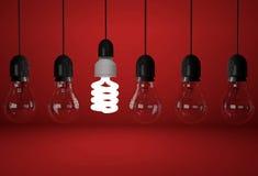 Ampoule incandescente et une économiseuse d'énergie sur le fond rouge Photo stock