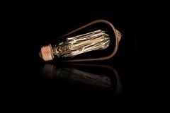 Ampoule incandescente sur le noir images stock