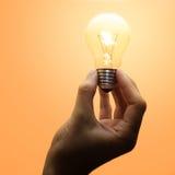 Ampoule luminescente dans la main humaine Photographie stock