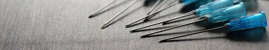 Background with ampoule and needles from a medical syringe Royalty Free Stock Photos