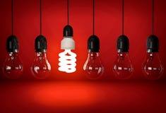 Ampoule rougeoyante d'économie d'eco accrochant sur le fil dans la rangée de b incandescent Photos libres de droits