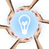 Ampoule rougeoyante entourée à la main Images libres de droits