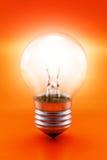 Ampoule rougeoyante sur le rouge Images stock