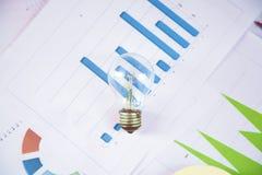 Ampoule sur le graphique sur le bureau photos stock