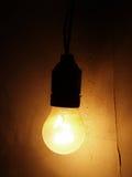 Ampoule sur un mur foncé Images libres de droits