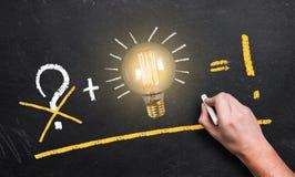 Ampoule sur un tableau noir et une main avec la craie faisant une équation du succès image stock