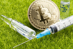 Ampoule and syringe with bitcoin coin - healthcare cost concept Royalty Free Stock Photography