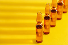 Ampoules. On a yellow background Stock Photography