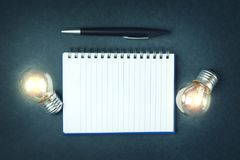 Ampoules avec le bloc-notes et le stylo image stock