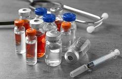 Ampoules avec le vaccin, la seringue et le stéthoscope photos libres de droits