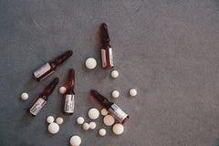 Ampoules B12 et pilules blanches sur la table concr?te images libres de droits