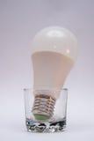Ampoules blanches dans un verre-verre sur un fond blanc Photos stock