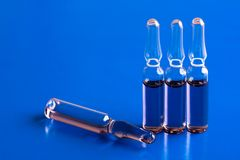 Ampoules on blue background. Four medical ampoules on a blue background Royalty Free Stock Image