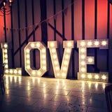 Ampoules de Word de signe d'amour contre le mur de grange Photos stock