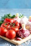 Ampoules fraîches d'ail de tomates sur la photo de verticale de conseil en bois Images stock