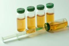 Ampoules médicales avec le vaccin et la seringue sur le fond blanc Image stock