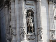 Ampuła kamienia postać na fasadzie Muzealny budynek w louvre, Paryż zdjęcia royalty free
