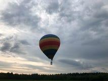 Ampuła barwiąca jaskrawa round tęcza barwił pasiastego pasiastego latanie balon z koszem przeciw niebu w wieczór zdjęcie royalty free