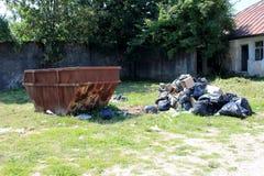 Ampuła rdzewiał stary otwartego opróżnia grata śmietnika z stosem śmieci w otwartych i rozdzierających czarnych plastikowych work obrazy royalty free