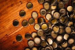 Ampuła stos piwnej butelki nakrętki na drewnianym biurku Zdjęcia Royalty Free