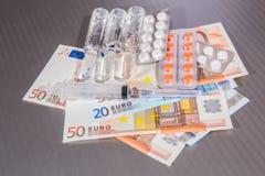 Ampułki, strzykawka i pastylki, kłamają na cudzoziemskich banknotach zdjęcie stock
