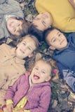 Ampuły grupa dzieci Szczęśliwi dzieci kłama na spada liściach Obraz Stock
