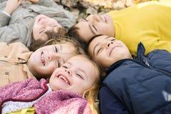 Ampuły grupa dzieci Szczęśliwi dzieci kłama na spada liściach Obraz Royalty Free