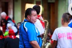 AMPUERO, SPANJE - SEPTEMBER 10: De niet geïdentificeerde musicus met een saxofoon vóór de Stier loopt op de straat tijdens festiv Stock Afbeeldingen