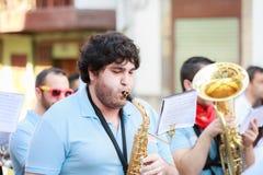 AMPUERO, SPANJE - SEPTEMBER 10: De niet geïdentificeerde musicus met een saxofoon vóór de Stier loopt op de straat tijdens festiv Stock Afbeelding