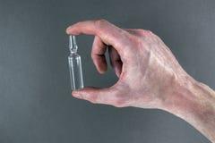 Ampul in een hand op een lichtgrijze achtergrond Stock Afbeelding
