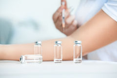 Ampules against patient doing injection Royalty Free Stock Images