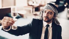Ampulheta aumentada árabe acima e olhando neles fotos de stock